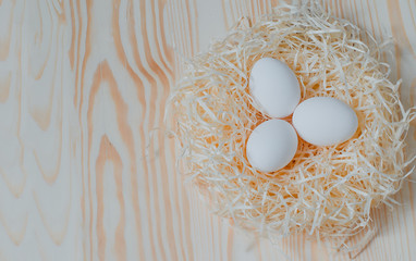 Three white chicken eggs  in a nest of straw on a light background with a wood  texture. Image for the Easter celebration with copyspace for text. Top view.