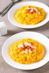 Hausgemachter Karottenrisotto zubereitet mit pürierten Möhren, serviert mit gerösteten Möhren und Käse, fotografiert mit natürlichem Licht (Selektiver Fokus, Fokus ein Drittel in das Bild)