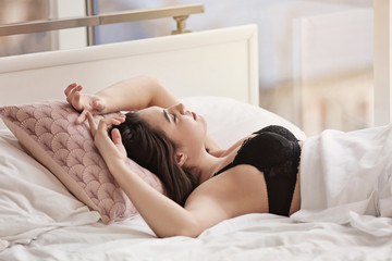 Young sexy woman waiting for her lover in bed