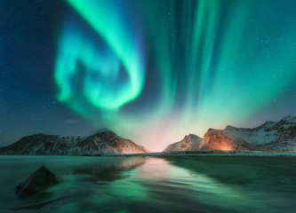 Tuinposter Noorderlicht Aurora borealis in Lofoten islands, Norway. Aurora. Green northern lights. Starry sky with polar lights. Night winter landscape with aurora, sea with sky reflection, stones, beach and snowy mountains