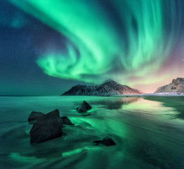 Tuinposter Landschappen Aurora. Northern lights in Lofoten islands, Norway. Sky with polar lights, stars. Night winter landscape with aurora, sea with sky reflection, stones, sandy beach and mountains. Green aurora borealis