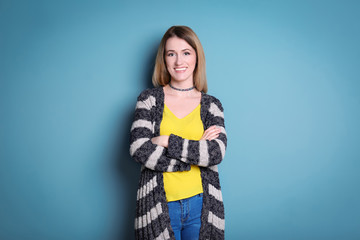 Wall Mural - Young woman in striped cardigan on color background