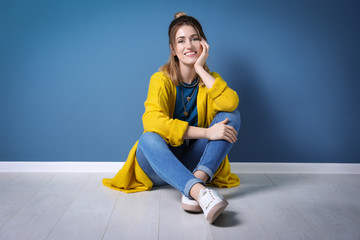 Wall Mural - Young woman in yellow cardigan sitting near color wall