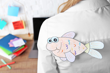 Paper fish on woman's back, closeup. April fool's day celebration