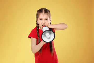 Little girl shouting into megaphone on color background