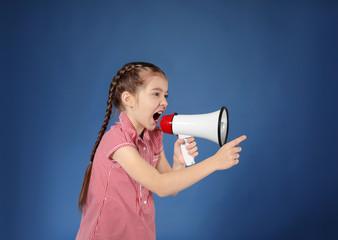 Emotional little girl shouting into megaphone on color background