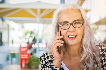 Thoughtful attractive elderly woman with long hair sitting listening to a phone call on her smartphone