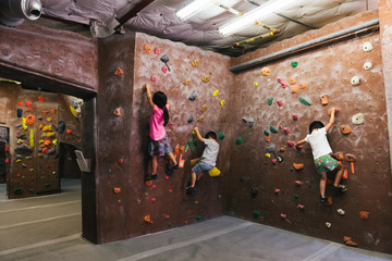 Elementary aged Asian children bouldering on rock climbing wall indoors
