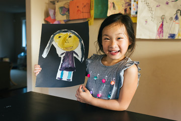 Young Asian American girl showing off self-portrait artwork