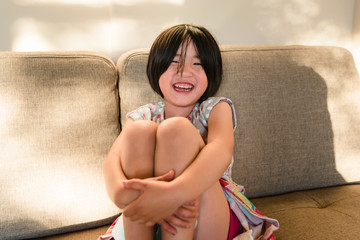 Asian American little girl laughing while clutching knees to chest
