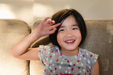 Young girl sitting on couch smiling moving bangs out of face