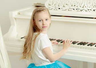 Caucasian little girl with long blond hair, in a beautiful pink