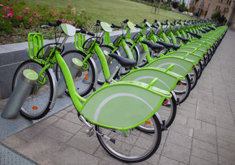 Row of new green public sharing bicycle lined up on the street , Modern concept of ecological transportation, Bike urban transport