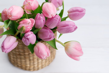 Bouquet of pink tulips in a wicker basket on light gray background