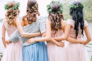 three bridesmaids in powdery dresses transformers and wreaths on the head embrace the bride in a blue dress