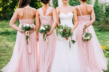 three bridesmaids in powdery dresses transformers with bouquets in hands stand with their backs near the bride in a white dress with a wedding bouquet in her hand on a green lawn