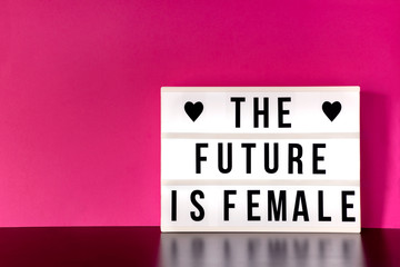 "International Women's Day - concept - 'Press for Progress' 2018 theme ""The Future is Female"" - light box with cinema style lettering on hot pink background with copy space"