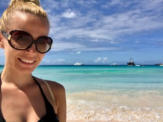Beautiful blonde woman in Barbados wearing a bikini at a untouched beach with crystal clear turquoise water and a blue sky