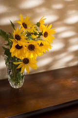 Bright yellow sunflowers in a crystal vase sitting on a wood table with sunshine coming through leaves against a gold wall