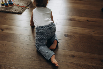 close-up of the baby's legs that creeps towards the toys on the wooden floor