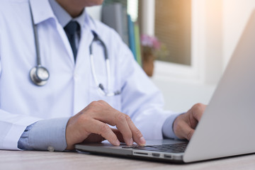 Doctor working on laptop computer, telemedicine