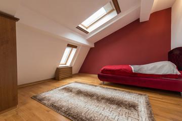 Bedroom interior in luxury red loft, attic, apartment with roof windows