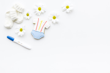 Pregnancy and preparation for childbirth. Pregnancy test near booties and flowers on white background top view copy space