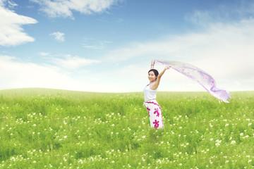 Carefree beautiful Asian woman holding fabric on green meadow