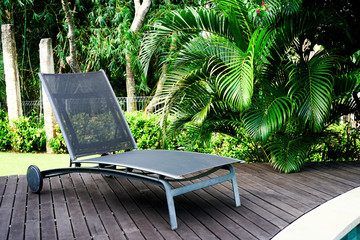 A chaise longue stands on a wooden floor near the pool. In the background are green palm leaves. Side view with copy space
