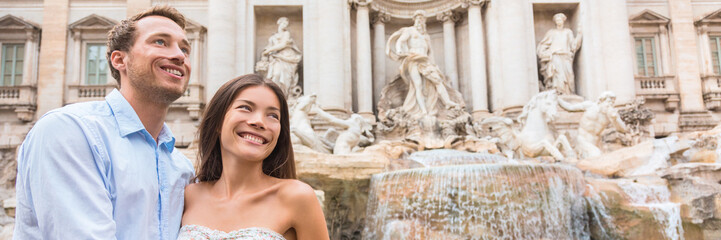 Wall Mural - Europe honeymoon summer holiday in Rome, Italy. Multiracial couple tourists sightseeing Trevi fountain. Travel elegant Asian woman with Caucasian man happy portrait banner panorama.