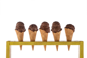 ice cream in waffle cones in rustic wood holder isolated on white background
