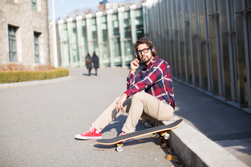 Handsome Man Listening on Headphones Next to Skateboard