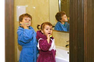 Cute kids in bathrobes in the bathroom brushing their teeth