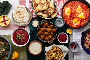 Overhead image of traditional jewish and middle eastern food: falafel, fattoush, tabouli, shakshuka, balila, hummus, roasted eggplants and spicy beetroot dip. Israeli cuisine concept