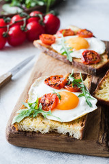 Breakfast toast with egg, arugula and roasted tomato, closeup view. Vertical
