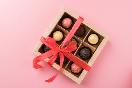 A set of assorted chocolates in a paper box with a satin pink ribbon on a pastel background.Flat layout.