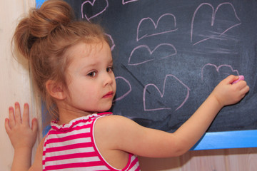 A child draws hearts on a slate. A little girl draws a heart on a blackboard.