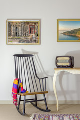 Interior shot of vintage rocking chair and old radio on old style vintage table on background of off white wall with two hanged paintings including clipping path for paintings