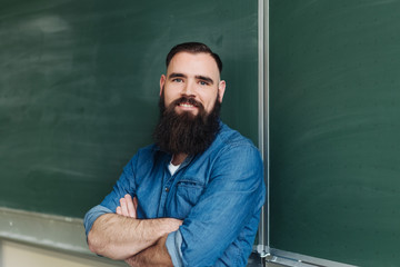 Smiling bearded man standing by blackboard