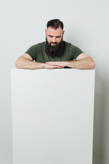 Bearded man standing over blank white banner