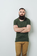 Bearded man standing by bright wall