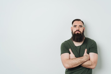 Bearded man standing against bright background