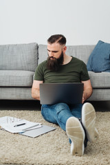 Man sitting of floor next to sofa with laptop
