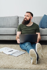 Bearded man sitting working on a rug at home