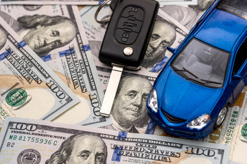 Keys to the car and car that are lying on 100 dollar bills