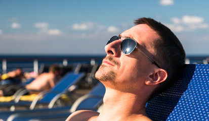 Headshot of a man wearing sunglasses laying on a beach lounge chair on the deck of a cruise ship.
