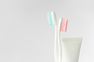 Close up of two plastic white toothbrushes with pink and blue bristle and toothpaste in tube on white background. Free copy space.
