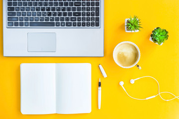 Workplace with a biclone, pen, headphones, a cup of coffee and green whiskers in white pots. The working space of a freelancer. Bright yellow background. Top view. Flat lay. Copyspace Wall mural