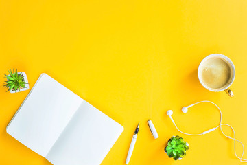 Workplace with a biclone, pen, headphones, a cup of coffee and green whiskers in white pots. The working space of a freelancer. Bright yellow background. Top view. Flat lay. Copyspace