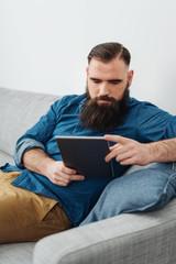 Bearded man using digital tablet on sofa